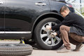 Man changing his spare wheel replacing the original tyre with a fixed puncture tightening the nuts with a spanner Stock Images