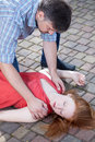 Man checking up consciousness of young girl lying on pavement Stock Photo