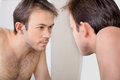 Man checks his reflection in the mirror in early morning Stock Photo
