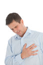 Man with chest pains grimacing in agony as he experiences the first signs of a heart attack or infarct Royalty Free Stock Photo