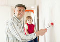 Man with child paints wall brush at home Royalty Free Stock Photos
