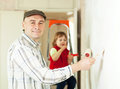Man with child paints wall at home Stock Images