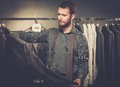 Man choosing jacket at shop handsome with beard in a Royalty Free Stock Photos