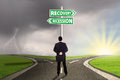 Man choosing the road to recovery or recession finance male entrepreneur standing on and look at a signpost while Royalty Free Stock Photography