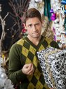Man with christmas gift biting lips in store portrait of young Stock Photos