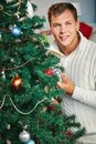 Man by christmas tree happy in pullover looking at camera out of decorated firtree Royalty Free Stock Photography