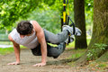 Man in city park doing suspension trainer sport young exercising with sling under summer trees for fitness Stock Images