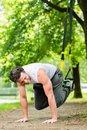 Man in city park doing suspension trainer sport young exercising with sling under summer trees for fitness Stock Image
