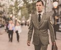 Man classic grey suit briefcase walking outdoors Royalty Free Stock Image