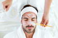 Man with clay facial mask in beauty spa. Royalty Free Stock Photo