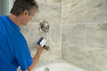 Man cleaning bathtub tiles and fixtures with scrub brush Royalty Free Stock Photo