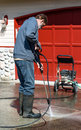 Man cleaning driveway with pressure washer spring white male vertical copy space Royalty Free Stock Photography