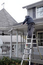 Man cleaning eaves troughs a homeowner tackles the chore of out the during late fall Royalty Free Stock Photography