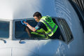Man cleaning jet plane windows workman in green vest leans out of commercial cockpit and cleans window windshield with blue cloth Stock Photo