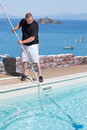 Man cleaning swimming pool above the sea photo of a situated with island in background Royalty Free Stock Photos