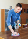 Man cleaning table with rag and cleanser european in home Stock Photo