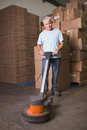 Man cleaning warehouse floor with machine portrait of Stock Photos