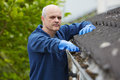 Man clearing leaves from guttering of house Stock Photos