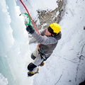 Man climbing frozen waterfall winter time Royalty Free Stock Images