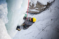 Man climbing frozen waterfall winter time Royalty Free Stock Image