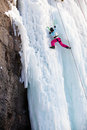 Man climbing frozen waterfall winter time Stock Image