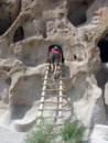 Man climbing ladder at cliff dwellings Stock Photos
