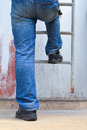 Man climbing ladder worker wearing blue jeans Royalty Free Stock Image