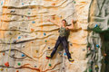 Man climbing on man made cliff in the sport centre Royalty Free Stock Images