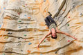 Man climbing on man made cliff in the sport centre Stock Photos