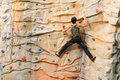 Man climbing on man made cliff in the sport centre Stock Images