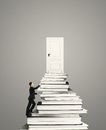 Man climbing on stack of books young with door Royalty Free Stock Images