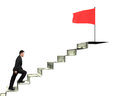 Man climbing to top for red flag on money stairs Royalty Free Stock Photo