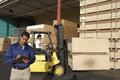 Man with clipboard in front of forklift stacking boxes male supervisor at warehouse Royalty Free Stock Image
