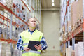 Man with clipboard in safety vest at warehouse wholesale logistic people and export concept reflective Royalty Free Stock Photos