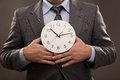Man with clock young in a suit holding a Royalty Free Stock Image