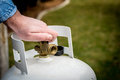 Man closes a knob on a propane tank valve being closed Royalty Free Stock Images