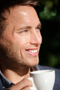 Man closeup portrait at cafe drinking coffee smiling happy handsome male model enjoying espresso outdoor in sun Royalty Free Stock Photos