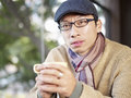 Man in coffee shop with peaked cap and scarf holding cup looking at camera Royalty Free Stock Photo