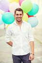 Man with colorful balloons in the city summer holidays celebration and lifestyle concept Royalty Free Stock Photo