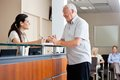 Man communicating with female receptionist senior men while women sitting in background Royalty Free Stock Images