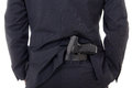 Man concealing gun in pants behind his back isolated on white background Stock Photos
