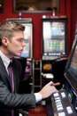 Man concentrate on slot machine young gambling the in casino Royalty Free Stock Image