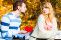 Man confess love to girl on bench in park confessing and affection with romantic gesture rejection and disapproval negative Stock Image