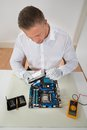 Man connecting harddisk with the motherboard young at desk Royalty Free Stock Photos