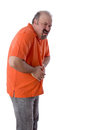 Man with constipation grimacing in pain middle aged as he clutches his stomach discomfit due to compaction of his feces and Stock Images
