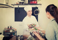 Man cook giving to waitress ready to serve salad Royalty Free Stock Photo