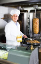 Man cook making kebab dish on kitchen in fast food restaurant Royalty Free Stock Photo