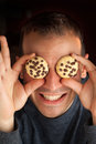 Man with cookie eyes crazy holds cookies over his Royalty Free Stock Photography