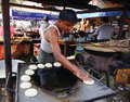 A man cooking cakes on street in Mandalay, Myanmar