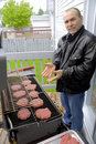 Man cooking hamburgers on a BBQ Stock Image
